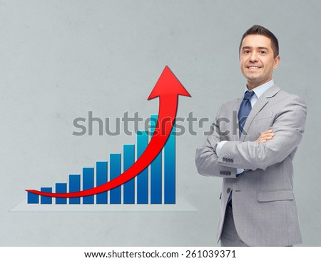 business, people, economics and financial success concept - happy smiling businessman in suit with growth chart over gray background