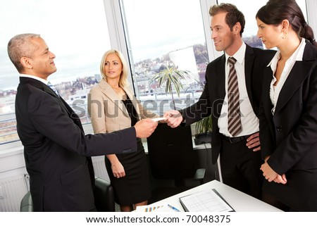 Business people exchange business cards - stock photo