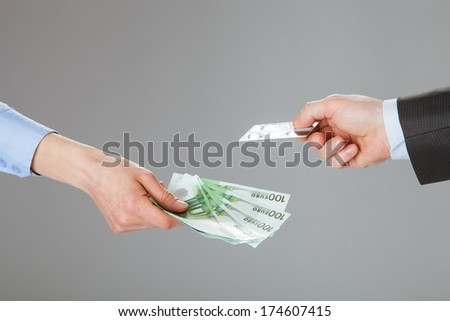 Business people exchanging credit card and money - closeup shot of hands - stock photo