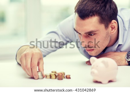 business, people, finances and money saving concept - businessman with piggy bank and coins at office - stock photo