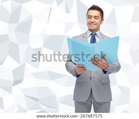business, people, finances and paper work concept - happy smiling businessman in suit holding open folder over gray graphic low poly background - stock photo
