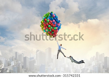 Business people flying in the sky on air balloon