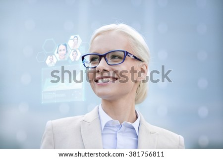business, people, future technology and communication concept - young smiling businesswoman in eyeglasses with virtual screen, video chat and charts projection outdoors - stock photo
