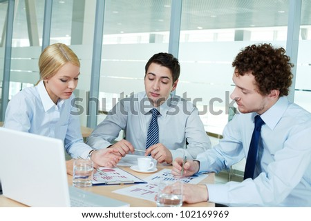Business people gathered to discuss documents - stock photo