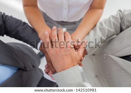 Business people gathering their hands together in the workplace - stock photo