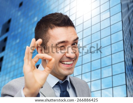 business, people, gesture and success concept - happy smiling businessman in suit showing ok hand sign over office building background - stock photo