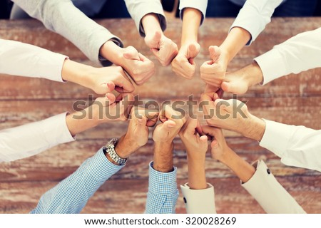 business, people, gesture and team work concept - close up of creative team showing thumbs up and sitting at table in office - stock photo