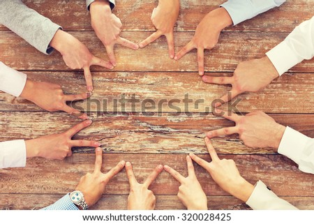 business, people, gesture and team work concept - close up of creative team showing victory hand sign on table in office - stock photo