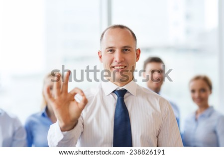 business, people, gesture and teamwork concept - smiling businessman showing ok sign with group of businesspeople in office - stock photo