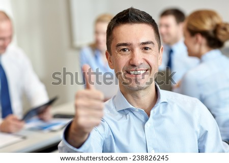 business, people, gesture and teamwork concept - smiling businessman showing thumbs up with group of businesspeople meeting in office - stock photo