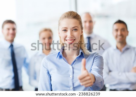 business, people, gesture and teamwork concept - smiling businesswoman showing thumbs up with group of businesspeople in office - stock photo