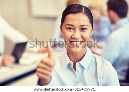 business, people, gesture and teamwork concept - smiling businesswoman showing thumbs up with group of businesspeople meeting in office - stock photo