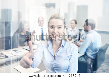 business, people, gesture and teamwork concept - smiling businesswoman showing thumbs up with group of businesspeople meeting in office