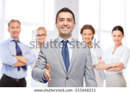 business, people, gesture, partnership and greeting concept - happy smiling businessman in suit with team over office room background shaking hand - stock photo