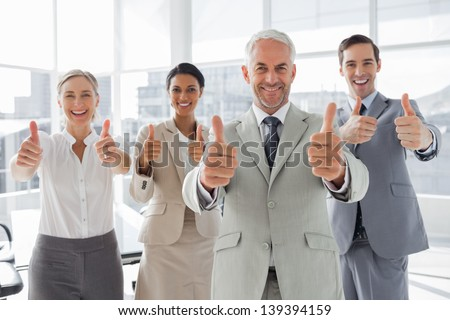 Business people giving thumbs up in the meeting room - stock photo