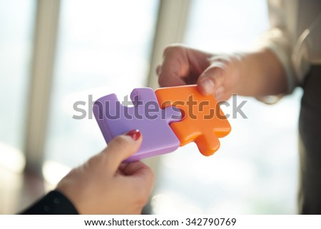 business people group assembling jigsaw puzzle and represent team support and help concept, top view perspective at modern bright office interior - stock photo