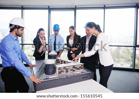 business people group on meeting and presentation  in bright modern office with construction engineer architect and worker looking building model and blueprint planbleprint plans - stock photo