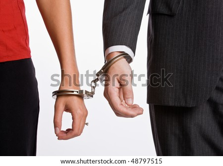 Business people handcuffed together - stock photo