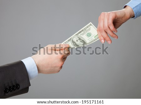 Business people hands exchanging money, closeup shot on grey background - stock photo