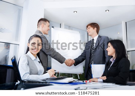 Business people handshake, businessmen hand shake on background, during meeting after signing agreement in office, businesswoman at desk smile