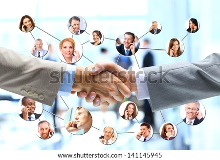 business people handshake with company team in background - stock photo