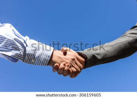 Business people handshaking on blue sky sunny outdoors background, close-up picture - stock photo