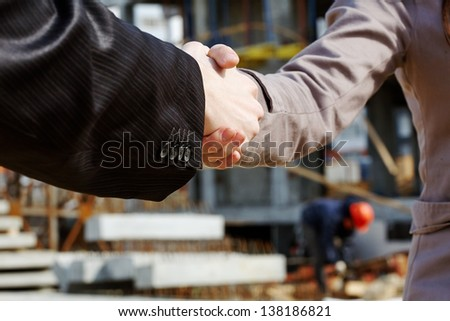 Business people handshaking while building - stock photo
