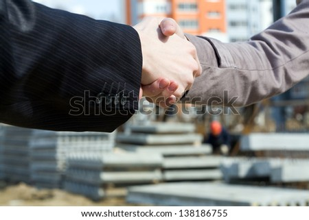 Business people handshaking while new building - stock photo