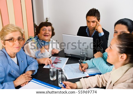 Business people having a funny conversation at meeting and working together,selective focus on elderly laughing woman