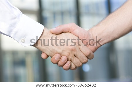 Business people having a handshake in front of office building. Man and woman trying to find a deal between office workers outdoors. - stock photo