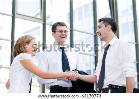 Business people having a handshake outdoors. Two men and a woman smiling to each other and they are ready to cooperate internationally.