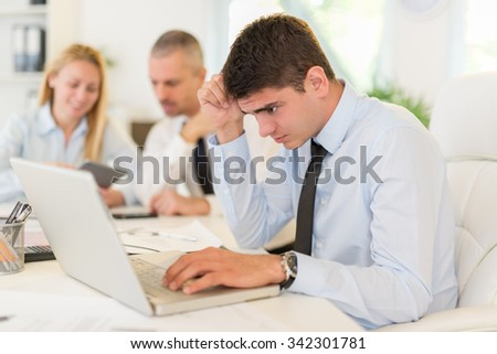 Business people having a meeting. Focus is on pensive young businessman who is worried looking at laptop. Selective focus.