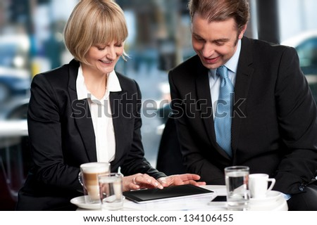 Business people having discussion at coffee table. Lady browsing on tablet device. - stock photo