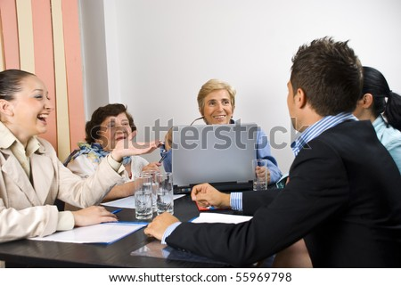 Business people having funny conversation at meeting and they smiling and laughing together,selective focus on senior blond woman - stock photo