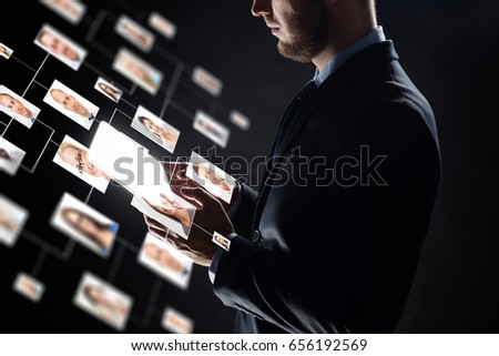 business, people, hiring, employment and future technology concept - close up of businessman with transparent tablet pc computer and contact icons over black background