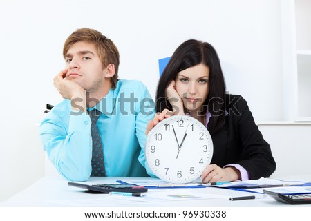 Business people hold clock, bored, tired Businessman and businesswoman sitting at the desk in office unhappy sad looking at camera - stock photo
