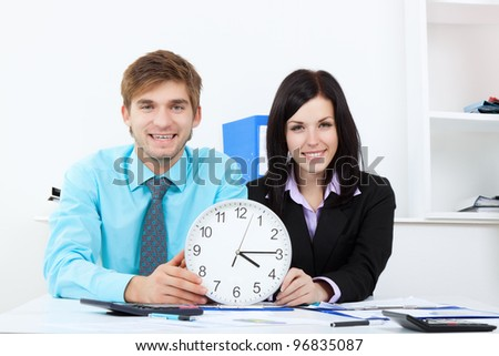 Business people hold clock, Businessman and businesswoman sitting at the desk in office, happy smile - stock photo