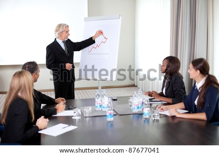 Business people holding a conference writing on an a board at a meeting room - stock photo