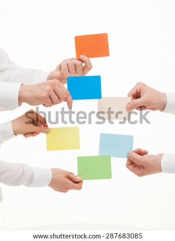 Business people holding colorful cards, white background