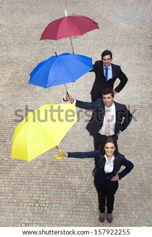 Business people holding colorful umbrellas outdoors - stock photo