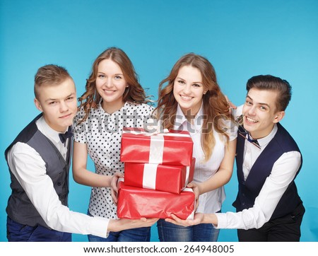Business people holding red gift boxes. Female and male model studio posing. Hipster Style - stock photo