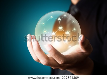 Business people holding social network in crystal ball - stock photo