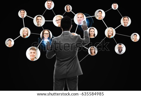 business, people, human resources, headhunting and technology concept - businessman working with network contacts icons from back over black background