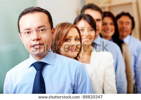 Business people in an office lead by a male