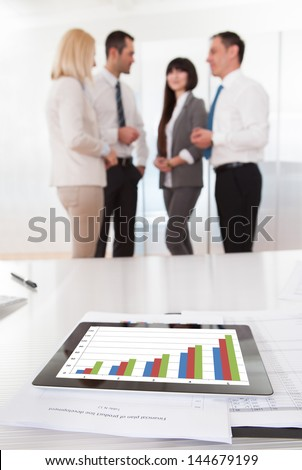 Business People In Conversation And Graph Chart On Table - stock photo