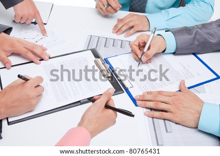 Business people in elegant suits sitting at desk working in team all together with documents sign up contract, holding clipboard, folder with papers, business plan. Isolated over white background. - stock photo