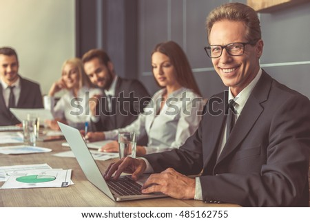 Business people in formal wear are discussing affairs at the conference. Handsome man in the foreground is using a laptop, looking at camera and smiling