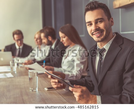 Business people in formal wear are discussing affairs at the conference. Handsome man in the foreground is using a digital tablet, looking at camera and smiling
