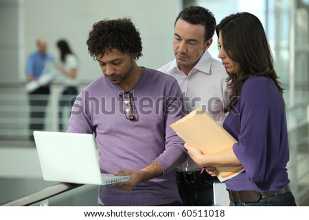 Business people in front of a laptop computer - stock photo