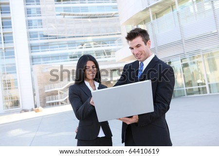 Business people in front of modern building with laptop computer - stock photo